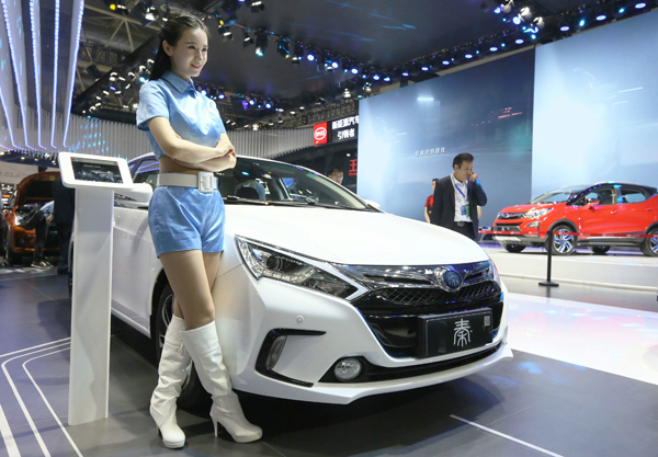A model stands beside a BYD car at an auto expo in Beijing. [Photo provided to China Daily]